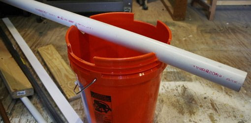 Cut bucket holding a piece of plastic PVC pipe for cutting.