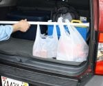 Using an expandable shower curtain rod to secure groceries in a car.