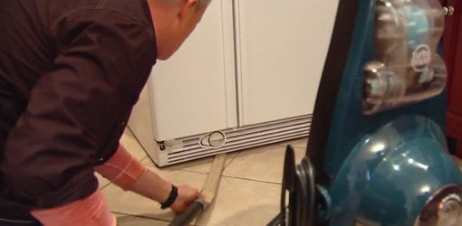 Using homemade vacuum attachment to clean under a refrigerator.