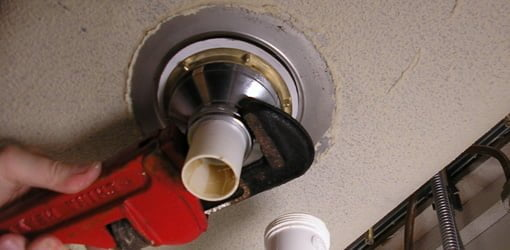 Using pipe wrench to tighten tailpiece drain pipe to sink strainer.