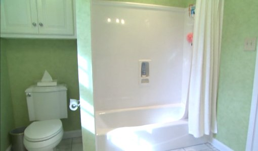 Remodeled bathroom with white toilet and tub and green walls.