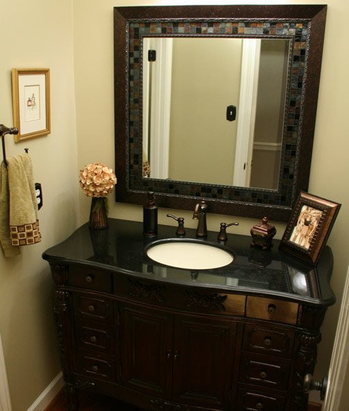 Stained wood vanity with black granite top and mosaic mirror.