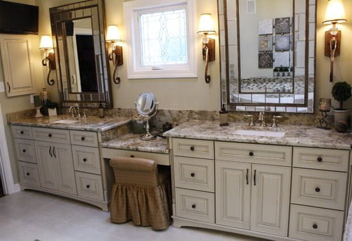 His and hers vanity with granite countertops and stained glass window.