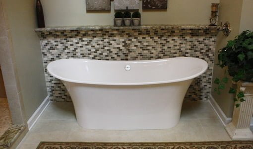 Master bathroom soaking tub with tile wall behind it after renovation.