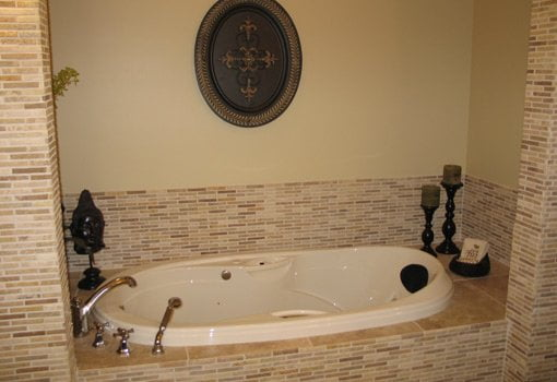 Updated bathtub with small tile surround.