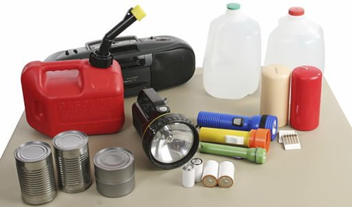 Emergency supply kit with water, flashlights, batteries, canned goods, radio, matches, candles, and gasoline.
