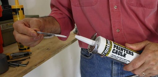 Using a nail to seal up the nozzle on a tube of caulking.