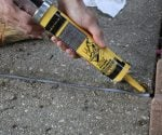 Using foam backer rod, followed by caulking, to fill a wide crack in a sidewalk.