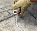 Applying concrete caulk to crack in patio.