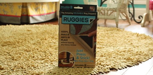 Box of Ruggies reusable rug grippers on rug.