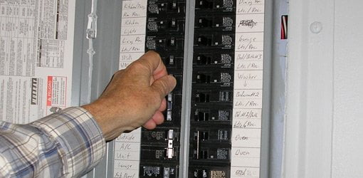 Turning a circuit breaker off in an electrical service panel.