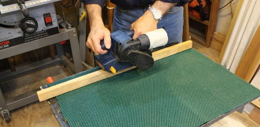 Using open weave shelf liner to hold boards in place for sanding.