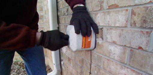 Attaching insulating foam cover to outdoor water spigot.