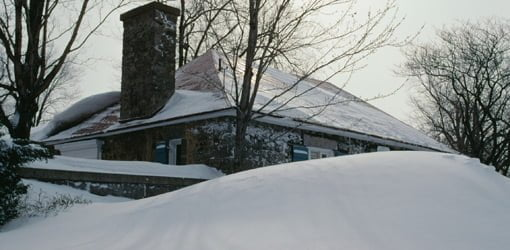 House covered in snow from winter storm.
