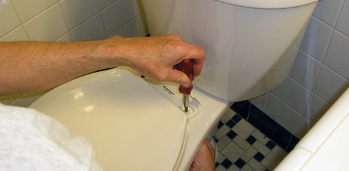Using screwdriver to tighten bolts on toilet seat.