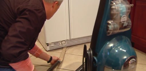Danny Lipford cleaning under a refrigerator.
