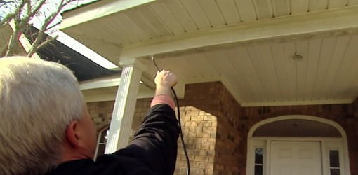 Spraying eaves on house to remove mold and mildew.