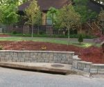 Completed stackable block retaining wall in front of house.