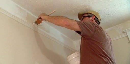 Allen Lyle using a brush to painting crown molding in a room.