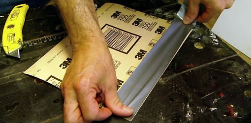 Reinforcing sandpaper by applying cloth duct tape to the back.