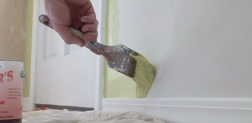 Painting wall with paintbrush.