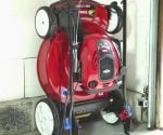 Toro SmartStow lawn mower stored vertically against garage wall.