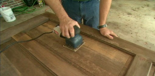 Using an oscillating sander to sand the old finish off an entry door.
