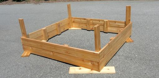 Upside down assembled sandbox with corner supports.