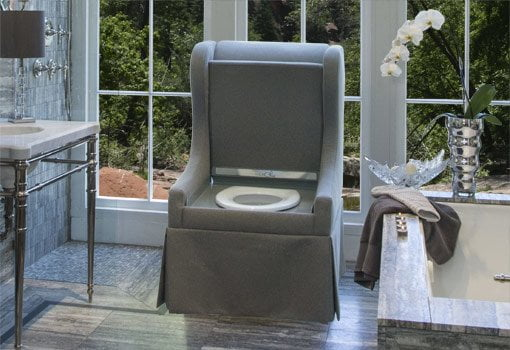 Gray upholstered chair toilet in bathroom.