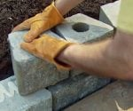 Laying the blocks for a stackable block retaining wall.