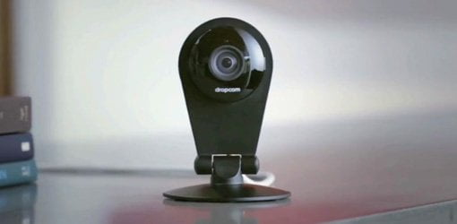 Nest Dropcam Pro security camera sitting on table next to books.