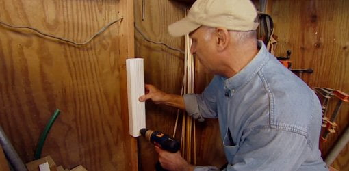 Using a cordless drill to attach a piece of vinyl downspout a wall stud.