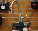 Delta Dominic kitchen faucet mounted on wall display in home center surrounded by other faucets.