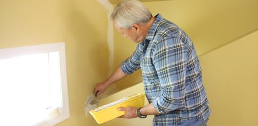 Danny Lipford using joint compound to repair cracks in yellow wall.