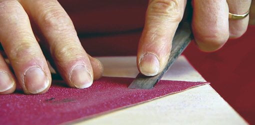 Using sandpaper to sharpen a chisel.