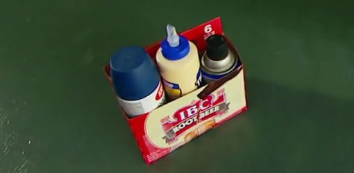 Six-pack carton filled with spray paint cans and glue bottles.