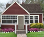 Outside of small house with red siding and white trim.
