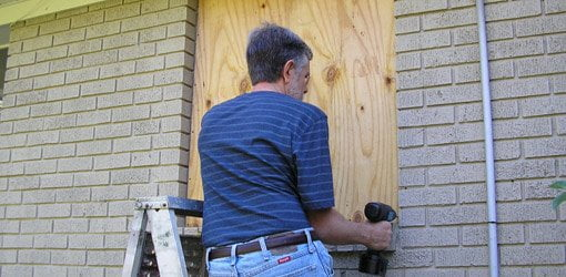 Man on stepladder covering windows with plywood.