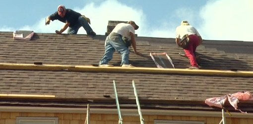 Roofers installing new roof after storm.