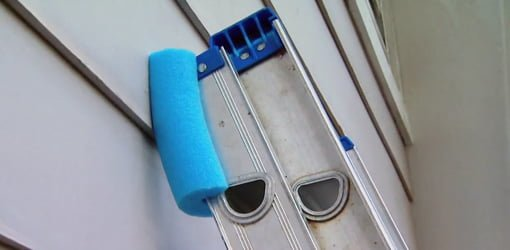 An extension ladder with protective foam covers made from a pool noodle.