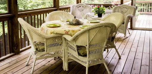 Screened deck with wicker furniture on it.