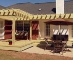 Completed wood pergola shade arbor on back of brick house.