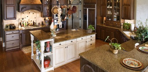 Kitchen with hanging pot rack, brown granite countertops, and white painted cabinets.