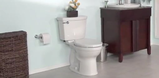White toilet in bathroom with blue walls and stained wood furniture style vanity.