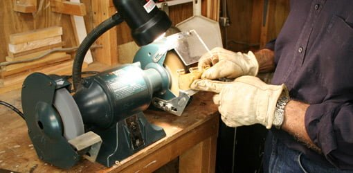 Using the wire wheel on a bench grinder to remove brass finish from hinges.