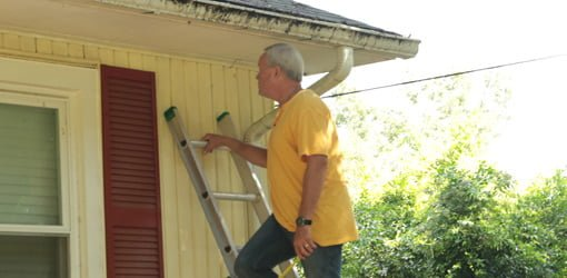 Danny Lipford on extension ladder preparing to clean gutters for winter.