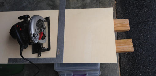 Plywood supported by 2x4s with circular saw and square.