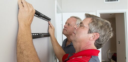Allen Lyle and Danny Lipford hang a wall-mounted TV.