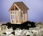 Model house surrounded by dollar bills