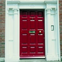 Red entry door with columns around trim.